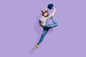 Portrait of active pretty girl in action jumping in the air showing perfect stretching making athletic ballet pose trick isolated on violet background holding hat in hands enjoying dreamday