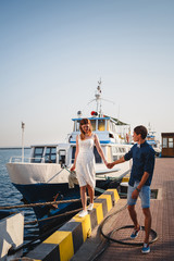 Cute young beautiful couple at pier at port with small yachts, hipster, happy smiling outdoor portrait