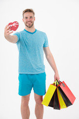 Happy man with heart and shopping bags isolated on white. Macho smile with colorful paper bags. Fashion shopper in blue tshirt and shorts. Valentines day preparation. Shopping sale and black friday