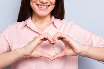 Cropped close up portrait of cheerful positive smiling woman in classic shirt with beaming smile making heart figure love symbol with fingers isolated on grey background