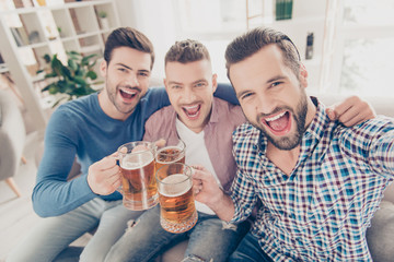 Portrait of stylish, best, attractive, modern positive guys with hairstyle, yelling, sitting on sofa in house, shooting selfie on smart phone, enjoying soccer word cup competition