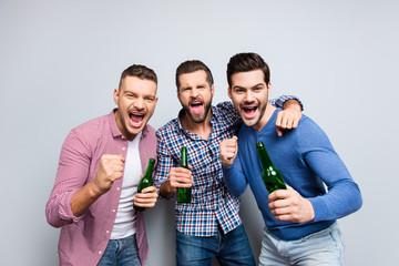 Portrait of cheerful, crazy, virile, harsh, funny guys with stubble and modern hairstyle yelling, having bottles with beer in hands, isolated on grey background, enjoying soccer word cup