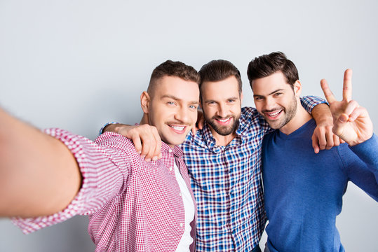 Self portrait of cheerful, positive, cool, stunning, virile, modern guys shooting selfie on smart phone, embracing, gesturing v-sign, isolated on grey background