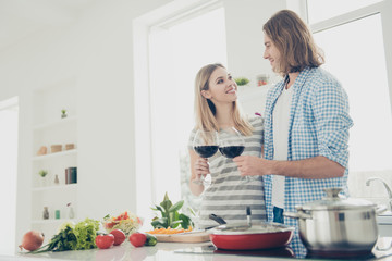 Bottom view of romantic lovely couple drinking alcohol beverage while preparing healthy dinner clinking glasses with wine standing in modern white kitchen looking at each other