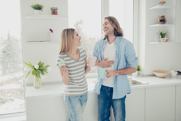 Portrait of cheerful positive couple having brunch in modern white kitchen drinking coffee eating dessert laughing sincere loudly having perfect mood