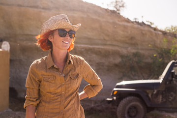 female working outdoor in a country farm near mountains. warm climate weather like far west. off road car in the background for alternative life concept in feeling with the nature and no stress