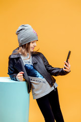 Cute pretty stylish girl in fashionable clothes taking selfie on yellow background.