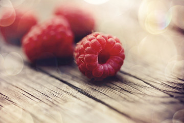 Ripe berries of raspberry lie on a wooden table.