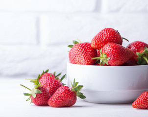 Heap of fresh strawberries in ceramic bowl on rustic white wooden background