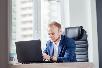 Businessman office worker enjoys a laptop in a modern workplace. smart watch .