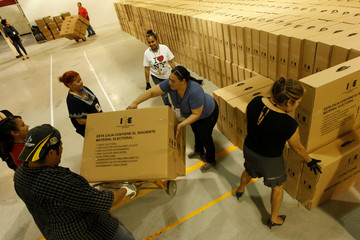 Employees of the Chihuahua state Electoral Institute move boxes with voting material to be distributed throughout the state at a warehouse in Ciudad Juarez