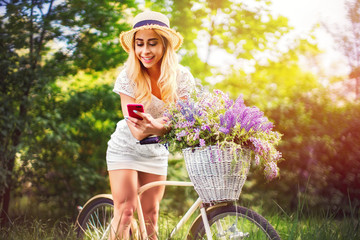 Portrait of a happy beautiful young girl with vintage bicycle and flowers using phone on city background in the sunlight outdoor. Bike with basket full of flowers. Active Leisure Concept.