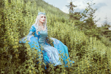 Beautiful elf woman sitting in the grass on a hill.