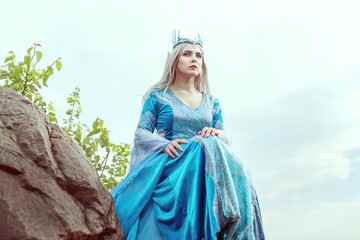 Beautiful elf woman in a blue dress is sitting on the mountain.