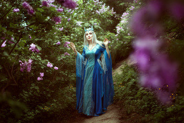Beautiful elf woman walks in a fairy forest among the lilac bushes.