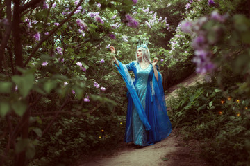 Young elf woman walks in a fairy forest among the lilac bushes.