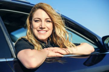 Smiling woman in the car on a summer day.