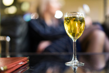 A glass of white wine against the background of a girl with a glass. The concept of going to a restaurant with a girl