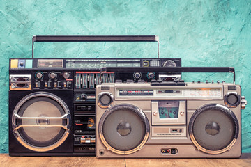 Retro designed ghetto blaster stereo boombox radio receivers with cassette recorders from circa 80s front textured aquamarine wall background. Listening music concept. Vintage old style filtered photo