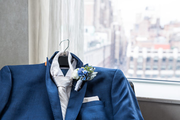 Men's suit and tie groom closeup with flower boutonniere, pin wedding preparation, pocket handkerchief, window with view of urban New York City NYC Manhattan cityscape, skyline