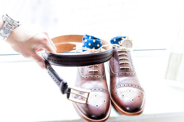 Man's hand arranging leather new brown shoes closeup still life isolated with blue polka dot socks, watch, shoelaces laces tied, wedding or interview preparation, belt on windowsill in room
