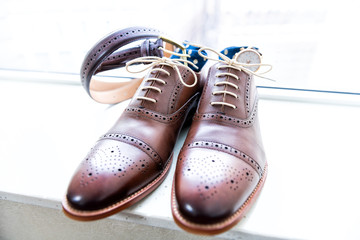 Men's new leather brown shoes closeup still life isolated with blue polka dot socks, watch, shoelaces laces tied, wedding or interview preparation, belt on windowsill in room