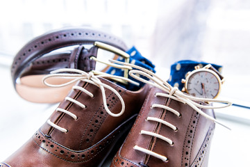 Men's new leather brown shoes macro closeup still life isolated with blue polka dot socks, watch, shoelaces laces tied, wedding or interview preparation, belt on windowsill in room