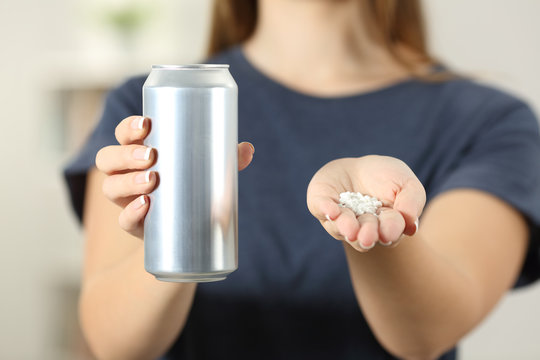 Woman hands holding a soda drink can and saccharin