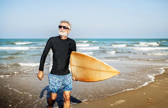 A senior man with a surfboard
