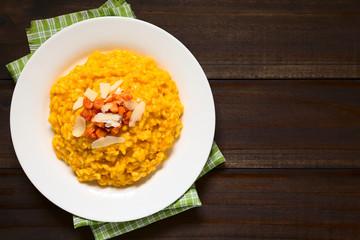 Hausgemachter Karottenrisotto zubereitet mit pürierten Möhren, serviert mit gerösteten Möhren und Käse, fotografiert mit natürlichem Licht (Selektiver Fokus, Fokus auf das Risotto)