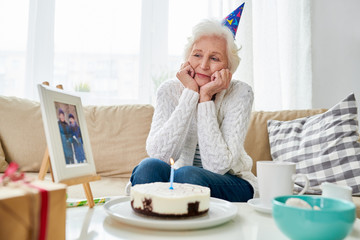 Portrait of lonely senior woman nervously celebrating birthday alone with photograph of her late husband on table by birthday cake photo in frame by me