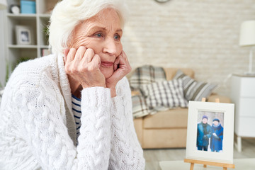 Portrait of lonely senior woman staring into space with tears in her eyes, sitting by picture of  her family, copy space (photo in frame by me)