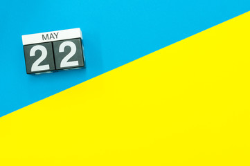 May 22nd. Day 22 of may month, calendar on blue and yellow background flat lay, top view. Spring time. Empty space for text