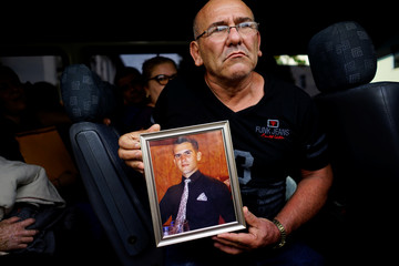 Mario Santos shows a picture of his late son Carlos Santos, who was killed in the Boeing 737 plane crash, as he leaves a funeral parlor in Havana