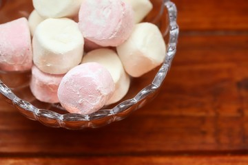 Pink And White Marshmallows In Glass Bowl On Wooden Table