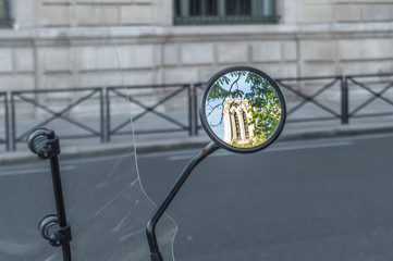 The mirror of a motorcycle reflecting the image of a tower of the Notre Dame Cathedral in Paris
