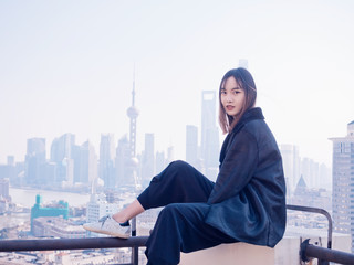 Beautiful young brunette woman sit on top of mansion roof with blur Shanghai Bund landmark buildings background. Emotions, people, beauty and lifestyle concept.