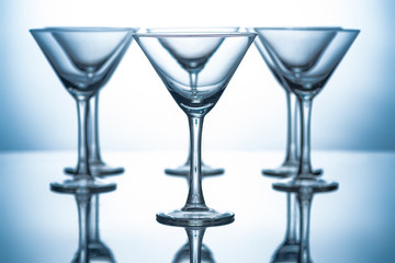 row of empty martini glasses on grey with reflections