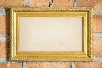 gold picture frame on the brick wall.