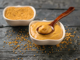 Two bowls and spoon with seeds and mustard sauce on a dark rustic table.
