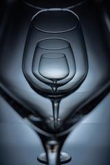 row of empty transparent wine glasses on grey