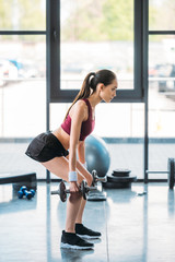 side view of asian sportswoman exercising with dumbbells at gym