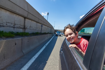 boy enjoys a trip by the car. smiling child peeking into the car window. copy space for your text