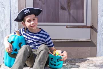boy with a teal bucket and teal pumpkin on the doorstep. Teal Pumpkin Project. Alternative non-food treats for kids with food allergies. the concept of health for children in the Halloween.