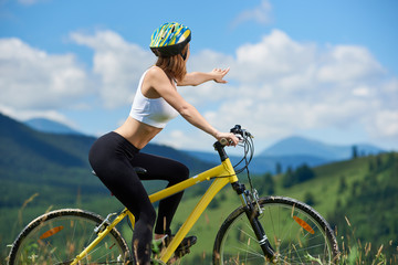 Attractive woman female riding on yellow mountain bicycle, wearing helmet, pointing at something in the distance, enjoying valley view on summer day. Mountains and blue sky on the blurred background