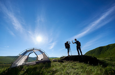 Two young people in backpacks and trekking sticks give each other a high five near the camping in the Carpathian mountains under the blue sky with a bright sun.