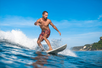 handsome sporty man having fun on surfboard on sunny day during summer vacation