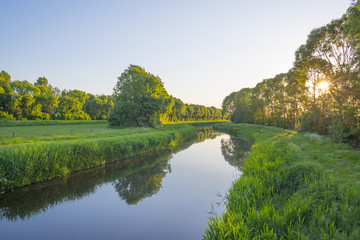 Canal in the countryside in the light of sunrise in spring