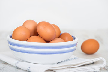 Cage free, brown eggs in a white and blue bowl on kitchen table. White background with copy space.