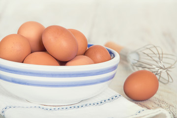 Cage free, brown eggs in a white and blue bowl on kitchen table. A whisk in the background.